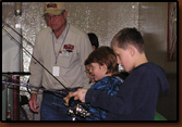 Vic Oma and Ed Naylor assist kids fishing at the Berkley Kids Aquarium at the 2009 Sports Show in Rapid City.