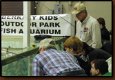 Ed Naylor and Vic Oma help kids at the free fishing aquarium at the 2009 Sports Show in Rapid City.