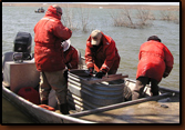Mike Johnson (far right) releases a tagged walleye while Denny Bohls places the next fish in the measuring trough. Rick Zimbelman (far left) prepares to tag the fish and Nancy Smidt records information. Volunteers assisted GF&P in this project at Orman Dam.