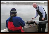 Not too cold for a hot lunch on the official's boat. Mike Johnson cooked burgers while Nancy Smidt supervised.