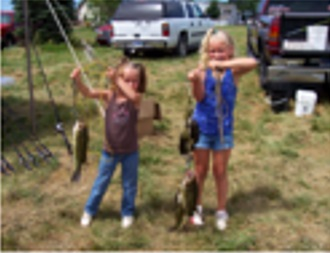 Two young girls showing off their fish