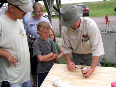 Michael Johnson demonstrates how to clean a trout to a couple successful anglers at the EAFB Party